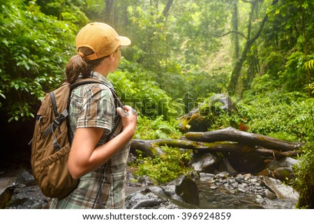 Young backpacker with backpack  traveling along rain forest. Lombok, Indonesia. Tourist hiking in the deep jungle