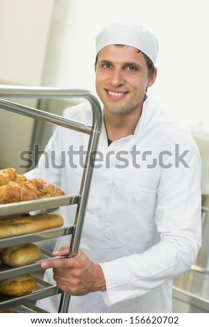 Young baker pushing a trolley with food on it while smiling at the camera