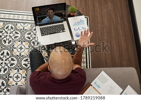 Photo of  Young bald entrepreneur actively gesturing when having online meeting with colleague,view from above