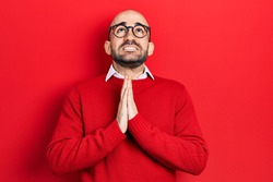Young bald man wearing casual clothes and glasses begging and praying with hands together with hope expression on face very emotional and worried. begging.