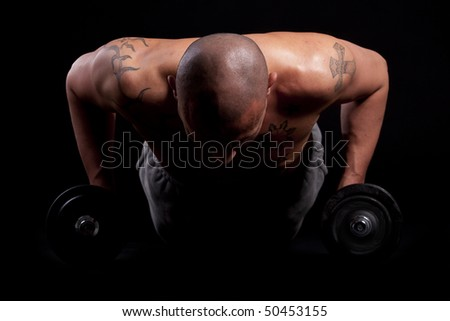 Young bald strong man is working out over black background.