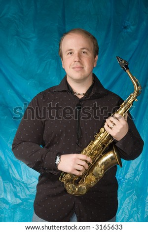 young balding man posing in front of portrait backdrop with saxaphone