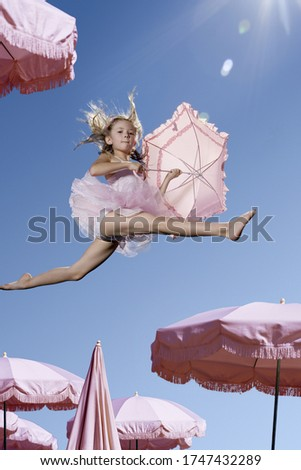 Young ballerina girl in mid air with umbrellas