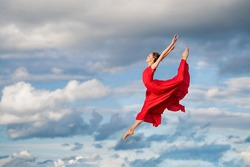 young ballerina in a bright red long dress soars in a jump above the ground, like a bird, against a background of blue sky and clouds. The skirt develops like wings.