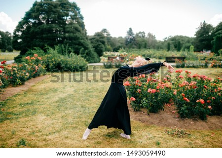 Young ballerina in black dress posing and showing ballet poses in summer park