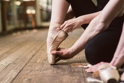 Young ballerina or dancer girl putting on her ballet shoes on the wooden floor. Male ballet dancer helps puttiing on. close-up.