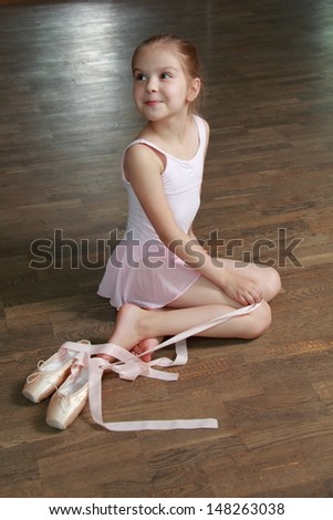 Young ballerina puts on pointe in ballet class at the old wooden dance floor