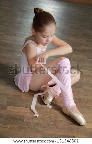 Young ballerina puts on pointe in ballet class at the old ...