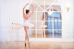 young ballerina standing on pointe in a tutu in a beautiful white hall in front of a mirror with her back to the viewer.
