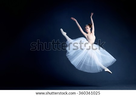Young ballerina with a perfect body is dancing in the photo studio. The dancer wears a fashionable dress. The photo is taken in minimal style, showing the beauty of a such classical art like ballet.