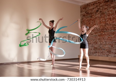 Young ballerinas in motion. Rhythmic gymnastics. Teenage sport, healthy teen lifestyle. Pretty girls with flying ribbons, dance class background, ballet concept