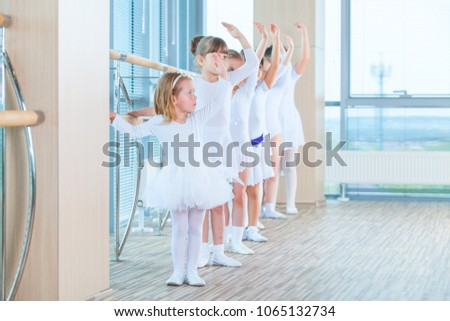 Stock Photo Young ballerinas rehearsing in the ballet class. They perform different choreographic exercises. They stand in different positions near the ballet barr.