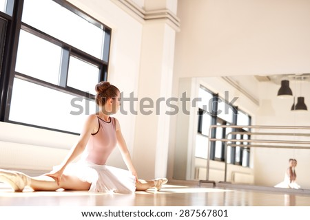Young Ballering Wearing Pink Tutu Doing Splits in Sunny Dance Studio and Monitoring Posture in Reflection in Mirror