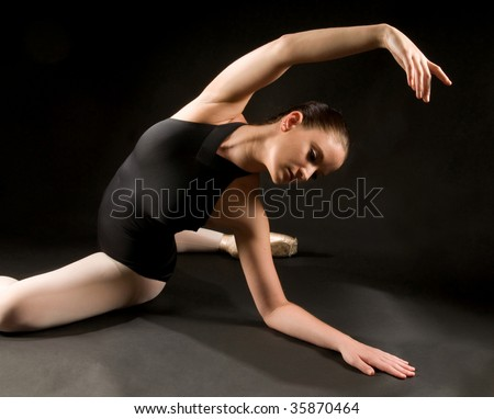 Young ballet dancer posing and stretching on the floor