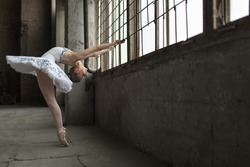 Young ballet dancer posing next to windows in an old industrial building. She is standing on pointes while she holds the grille during tilting back. Indoor. Horizontal.
