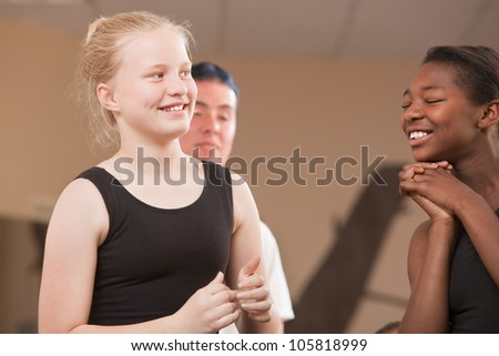Young ballet students laughing together at dance class