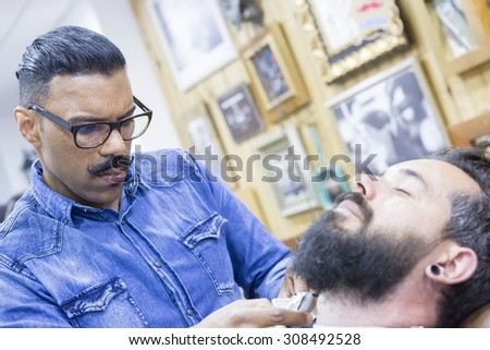 young barber is shaving a beard of a customer in a barber shop - focus between the barber eyes