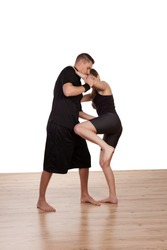 Young barefoot female kick boxer in training with her male instructor learning the moves as he demonstrates the technique