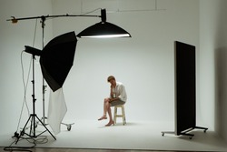Young barefoot man sits on chair in pose of thinker in photo studio. Male model wearing white shirt on white background among studio equipment and lighting fixtures. Backstage concept.