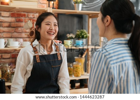 Young barista girl in apron and white shirt working at the counter in coffee shop. Nice smiling coffeehouse female staff taking order from customer in morning. businesswoman is regular client in cafe