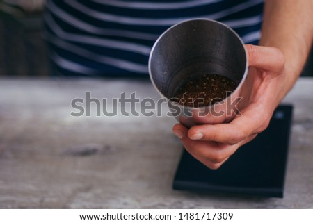 Young barista standing and show fresh coffee at coffee bar