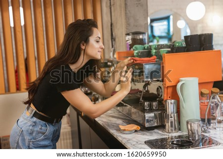 young barista woman cleaning professional coffee machine with dust , barist work routine.
