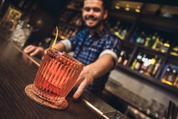 Young barman standing at bar counter prepared coktail close-up blurred background