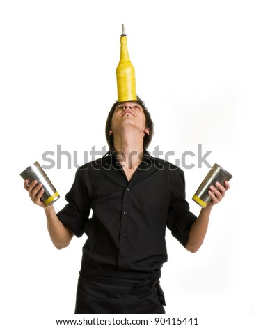 Young bartender does a trick with a shaker and bottle on white background - stock photo