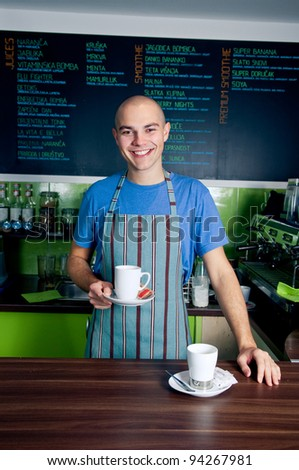 Young bartender smiling and holding cup of coffee.