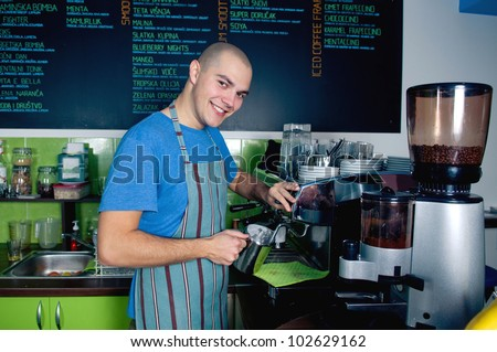 Young bartender smiling and making cup of coffee.