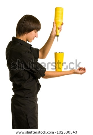 Young bartender with a shaker and bottle on white background