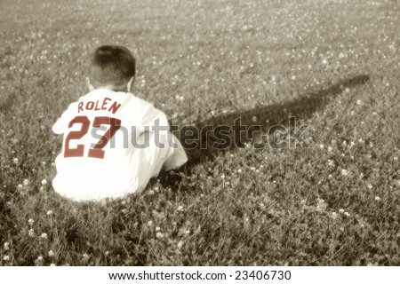 Young Baseball Boy Sitting in Grass