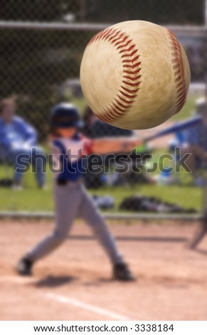 Young baseball player hitting a home run , focus on the ball with motion blur