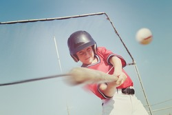Young baseball player hitting the ball.  Vintage instagram effect, motion blur on bat and ball