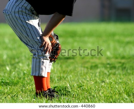 Young baseball player in outfield; space for copy.