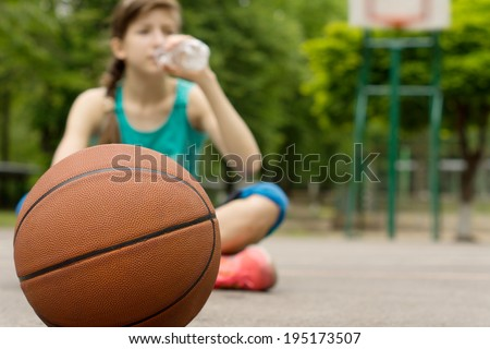 Young basketball player drinking water as she sits cross-legged on the court with the ball in front of her, focus to the ball