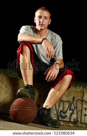 Young basketball player sitting down for a break, foot on the ball and looking at camera