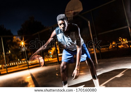 Young basketball player training in the street.