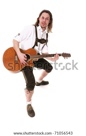 Young bavarian muscian in traditional costume playing guitar
