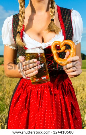 Young Bavarian woman drinking beer and keeping a pretzel in dirndl at meadow