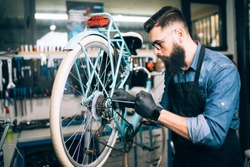 Young beard bicycle mechanic repairing bicycles in a workshop.