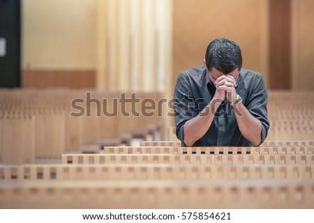 Shutterstock Young beard man wearing blue shirt praying in modern church