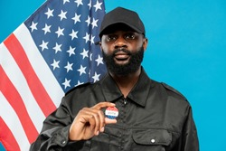 Young bearded African-american male security in black uniform showing vote insignia while looking at you against stars-and-stripes flag
