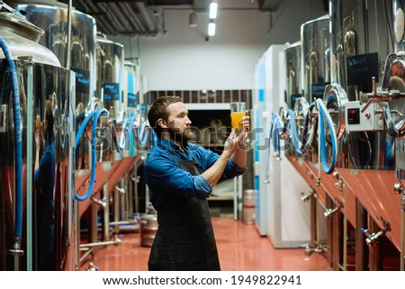 Young bearded brewery worker with glass of beer evaluating its visual characteristics after preparation while working in processing plant Сток-фото ©