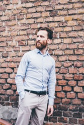 Young bearded business man outdoor leaning brick wall looking away pensive