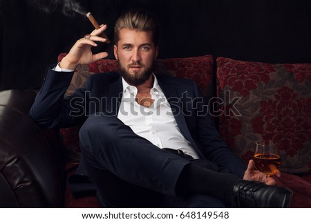 Young bearded businessman sitting on a couch with a alcoholic drink and a cigar