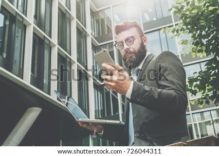 Young bearded businessman stands against modern building, uses smartphone and holds a laptop in his hand. Man works remotely. Distance job. Online marketing, education,training,e-commerce,e-learning.