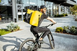Young bearded courier delivering food with a yellow thermal backpack, riding a bicycle in the city. Food delivery service concept