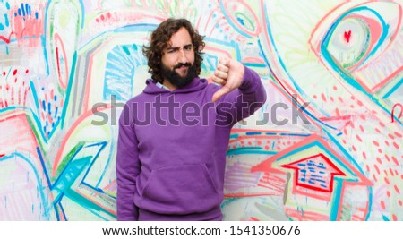 young bearded crazy man feeling cross, angry, annoyed, disappointed or displeased, showing thumbs down with a serious look against graffiti wall stock photo
