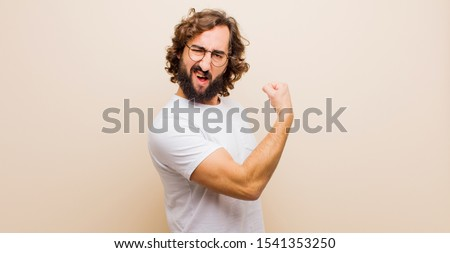 young bearded crazy man feeling happy, satisfied and powerful, flexing fit and muscular biceps, looking strong after the gym against flat color wall